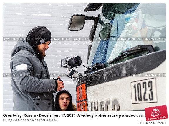 Купить «Orenburg, Russia - December, 17, 2019: A videographer sets up a video camera in front of the windshield of a truck cab», фото № 34126427, снято 17 декабря 2019 г. (c) Вадим Орлов / Фотобанк Лори
