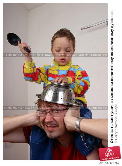 Отец затыкает уши, а сынишка колотит ему по железному дуршлагу, надетому на голову, фото № 69767, снято 4 июня 2007 г. (c) Harry / Фотобанк Лори