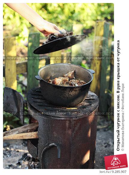 Купить «Открытый чугунок с мясом. В руке крышка от чугунка», фото № 9285907, снято 2 июля 2013 г. (c) Manapova Ekaterina / Фотобанк Лори