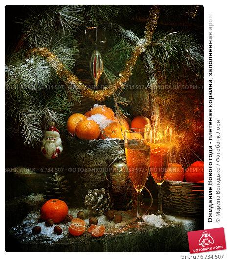Ожидание Нового года - плетеная корзина, заполненная ароматными спелыми мандаринами, и бокалы шампанского под пушистыми ветвями ели. Стоковое фото, фотограф Марина Володько / Фотобанк Лори