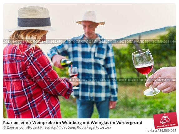 Paar bei einer Weinprobe im Weinberg mit Weinglas im Vordergrund. Стоковое фото, фотограф Zoonar.com/Robert Kneschke / age Fotostock / Фотобанк Лори