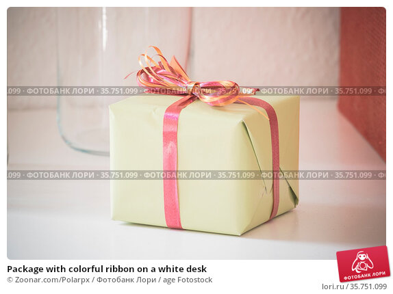 Package with colorful ribbon on a white desk. Стоковое фото, фотограф Zoonar.com/Polarpx / age Fotostock / Фотобанк Лори
