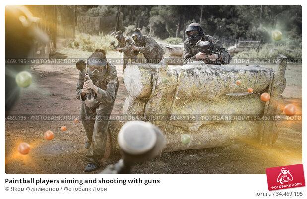 Paintball players aiming and shooting with guns. Стоковое фото, фотограф Яков Филимонов / Фотобанк Лори