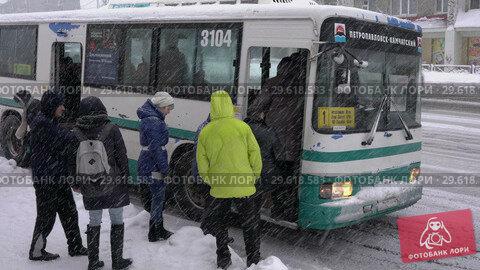 Купить «Пассажиры садятся в городской автобус во время зимней непогоды», видеоролик № 29618583, снято 26 декабря 2018 г. (c) А. А. Пирагис / Фотобанк Лори