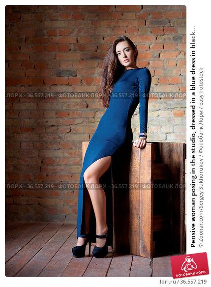 Pensive woman posing in the studio, dressed in a blue dress in black... Стоковое фото, фотограф Zoonar.com/Sergey Sukhorukov / easy Fotostock / Фотобанк Лори
