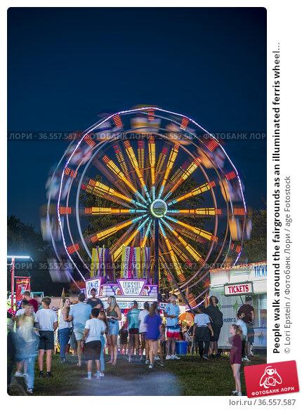 People walk around the fairgrounds as an illuminated ferris wheel... Редакционное фото, фотограф Lori Epstein / age Fotostock / Фотобанк Лори