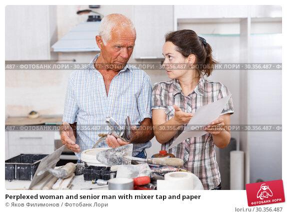 Купить «Perplexed woman and senior man with mixer tap and paper», фото № 30356487, снято 19 июня 2018 г. (c) Яков Филимонов / Фотобанк Лори