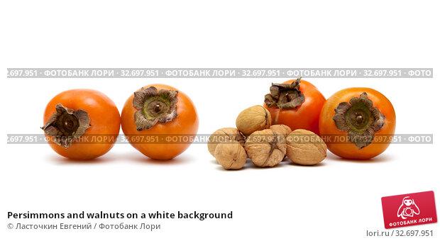 Persimmons and walnuts on a white background. Стоковое фото, фотограф Ласточкин Евгений / Фотобанк Лори
