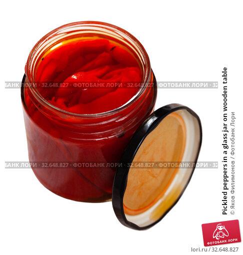 Купить «Pickled peppers in a glass jar on wooden table», фото № 32648827, снято 10 апреля 2020 г. (c) Яков Филимонов / Фотобанк Лори