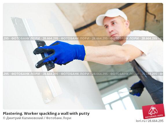Купить «Plastering. Worker spackling a wall with putty», фото № 28664295, снято 1 февраля 2018 г. (c) Дмитрий Калиновский / Фотобанк Лори