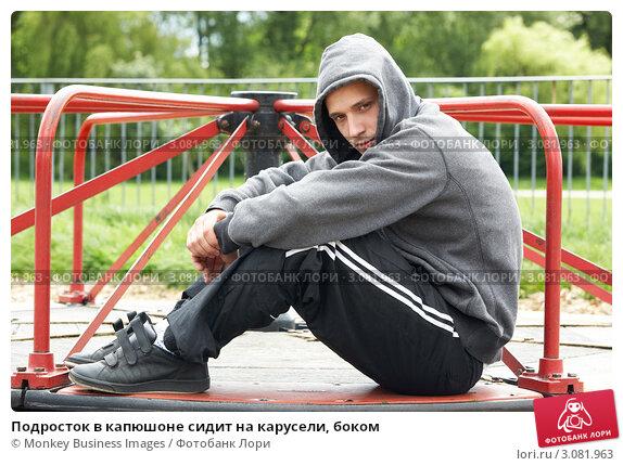Купить «Подросток в капюшоне сидит на карусели, боком», фото № 3081963, снято 21 мая 2009 г. (c) Monkey Business Images / Фотобанк Лори