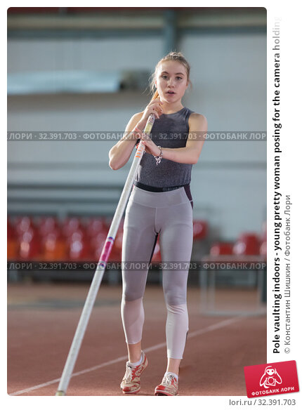 Купить «Pole vaulting indoors - young pretty woman posing for the camera holding a pole», фото № 32391703, снято 1 ноября 2019 г. (c) Константин Шишкин / Фотобанк Лори