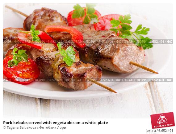 Купить «Pork kebabs served with vegetables on a white plate», фото № 6652491, снято 4 ноября 2014 г. (c) Tatjana Baibakova / Фотобанк Лори