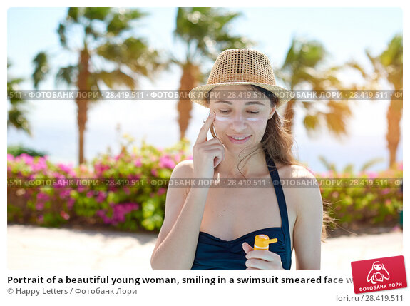Купить «Portrait of a beautiful young woman, smiling in a swimsuit smeared face with sun protection cream in hat on sea background. Concept: sea sun and travel vacation freedom, enjoy sunburn heat hot», фото № 28419511, снято 16 апреля 2018 г. (c) Happy Letters / Фотобанк Лори