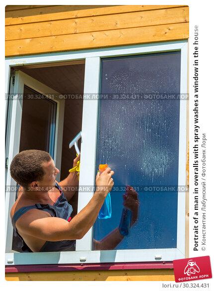 Купить «Portrait of a man in overalls with spray washes a window in the house», фото № 30324431, снято 23 июня 2016 г. (c) Константин Лабунский / Фотобанк Лори