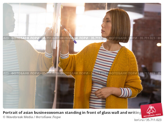 Portrait of asian businesswoman standing in front of glass wall and writing. Стоковое фото, агентство Wavebreak Media / Фотобанк Лори