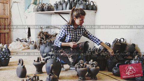 Купить «Portrait of cheerful female artisan inspecting finished production in pottery workshop», видеоролик № 32947543, снято 30 марта 2020 г. (c) Яков Филимонов / Фотобанк Лори