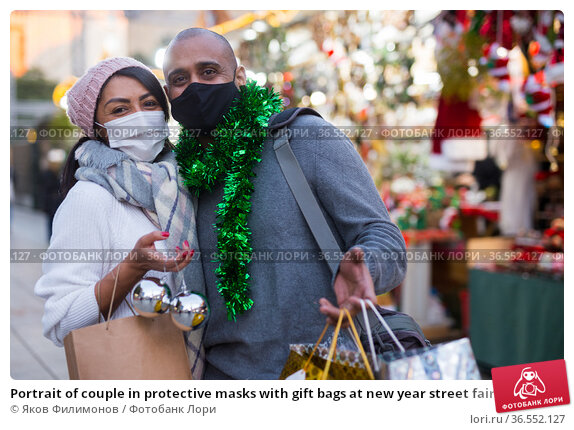 Portrait of couple in protective masks with gift bags at new year street fair. Стоковое фото, фотограф Яков Филимонов / Фотобанк Лори