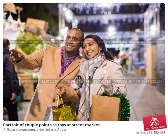 Portrait of couple points to toys at street market. Стоковое фото, фотограф Яков Филимонов / Фотобанк Лори