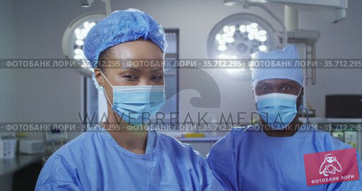 Portrait of diverse male and female surgeon wearing face masks standing in operating theatre. Стоковое видео, агентство Wavebreak Media / Фотобанк Лори