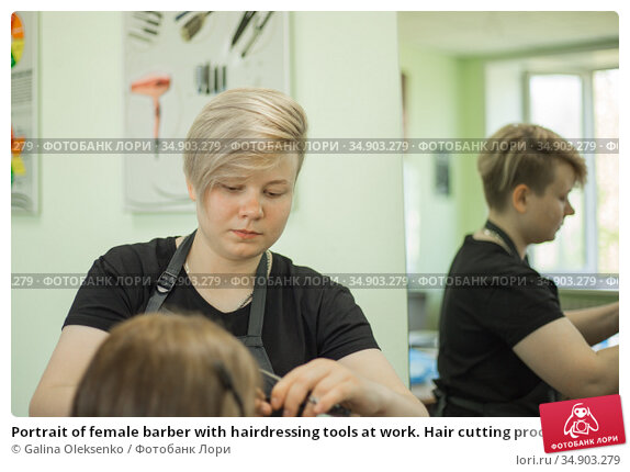 Portrait of female barber with hairdressing tools at work. Hair cutting process. Hairstyling in modern barbershop.Professional. Стоковое фото, фотограф Galina Oleksenko / Фотобанк Лори