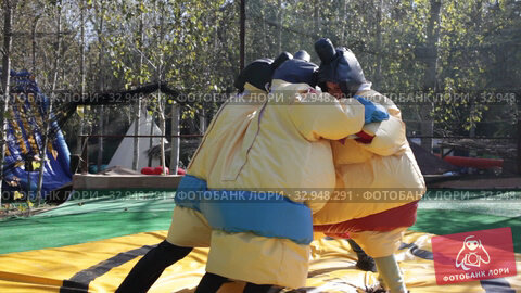 Portrait of happy exited men and women holding big boxing gloves on inflatable arena. Стоковое видео, видеограф Яков Филимонов / Фотобанк Лори