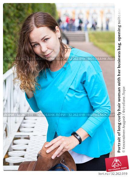 Купить «Portrait of long curly hair woman with her business bag, opening suitcase at bench in park», фото № 32262019, снято 24 августа 2019 г. (c) Кекяляйнен Андрей / Фотобанк Лори