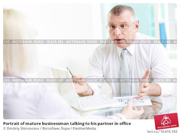Portrait of mature businessman talking to his partner in office. Стоковое фото, фотограф Dmitriy Shironosov / PantherMedia / Фотобанк Лори