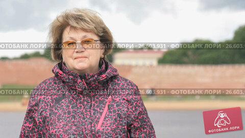 Купить «Portrait of smiling adult woman aged 60s outdoors», видеоролик № 26603931, снято 30 июня 2017 г. (c) worker / Фотобанк Лори