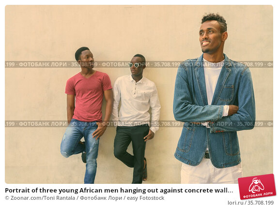 Portrait of three young African men hanging out against concrete wall... Стоковое фото, фотограф Zoonar.com/Toni Rantala / easy Fotostock / Фотобанк Лори