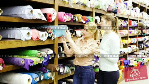 Portrait of two positive attractive girls choosing fabric among diversity on shelves in store. Стоковое видео, видеограф Яков Филимонов / Фотобанк Лори