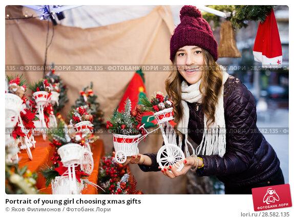 Купить «Portrait of young girl choosing xmas gifts», фото № 28582135, снято 22 декабря 2016 г. (c) Яков Филимонов / Фотобанк Лори