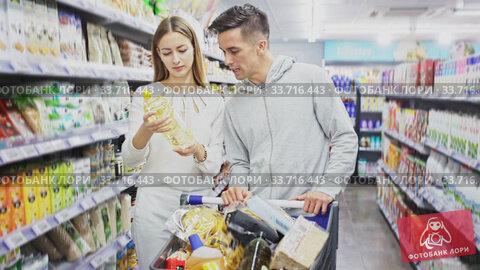 Portrait of young man and woman with shopping cart in supermarket. Стоковое видео, видеограф Яков Филимонов / Фотобанк Лори