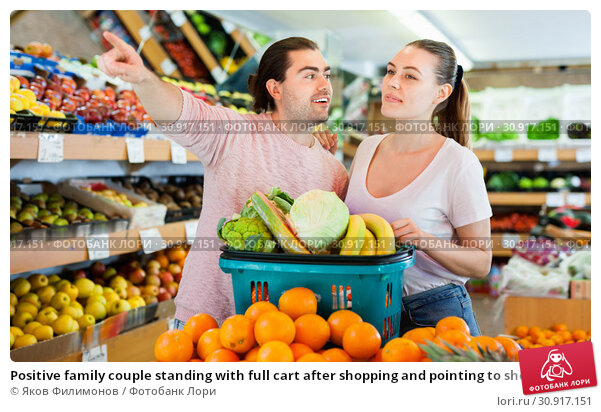 Купить «Positive family couple standing with full cart after shopping and pointing to shelves in fruit store», фото № 30917151, снято 27 апреля 2019 г. (c) Яков Филимонов / Фотобанк Лори