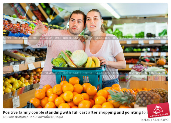 Positive family couple standing with full cart after shopping and pointing to shelves in fruit store. Стоковое фото, фотограф Яков Филимонов / Фотобанк Лори