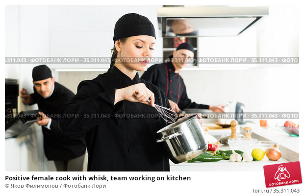 Positive female cook with whisk, team working on kitchen. Стоковое фото, фотограф Яков Филимонов / Фотобанк Лори