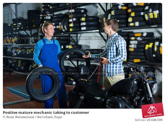 Купить «Positive mature mechanic taking to customer», фото № 29648599, снято 23 марта 2019 г. (c) Яков Филимонов / Фотобанк Лори