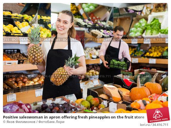 Positive saleswoman in apron offering fresh pineapples on the fruit store. Стоковое фото, фотограф Яков Филимонов / Фотобанк Лори