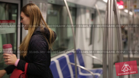 Купить «Positive young woman absorbed in her smartphone while traveling in subway car», видеоролик № 33045383, снято 17 января 2020 г. (c) Яков Филимонов / Фотобанк Лори