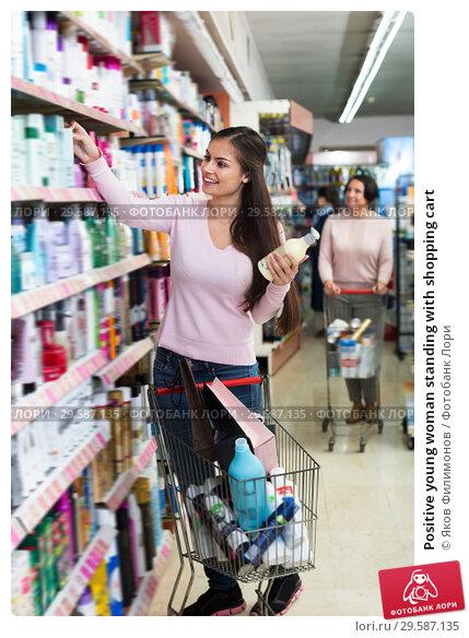 Купить «Positive young woman standing with shopping cart», фото № 29587135, снято 20 февраля 2019 г. (c) Яков Филимонов / Фотобанк Лори
