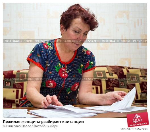 Купить «Пожилая женщина разбирает квитанции», эксклюзивное фото № 19557935, снято 27 декабря 2015 г. (c) Вячеслав Палес / Фотобанк Лори