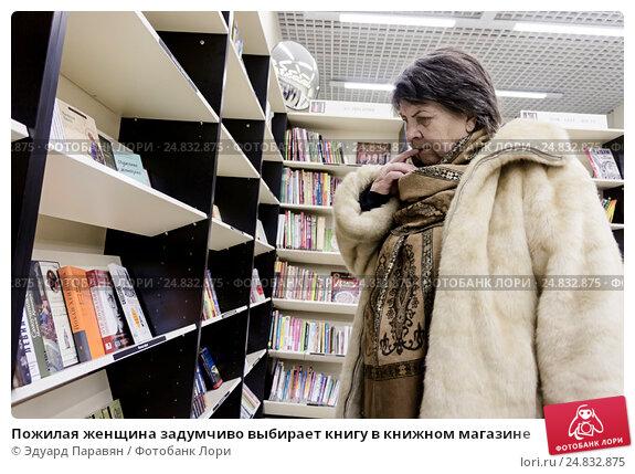 Купить «Пожилая женщина задумчиво выбирает книгу в книжном магазине», фото № 24832875, снято 6 января 2017 г. (c) Эдуард Паравян / Фотобанк Лори