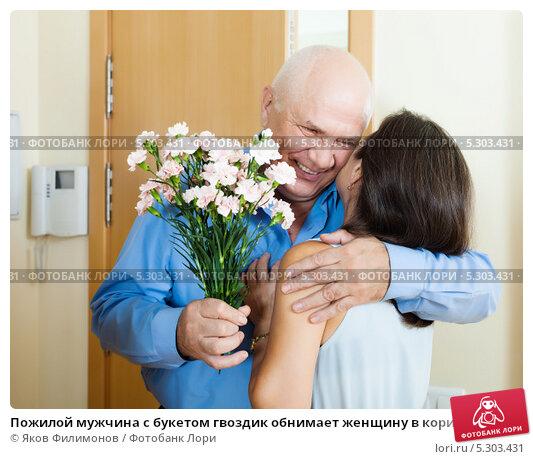Купить «Пожилой мужчина с букетом гвоздик обнимает женщину в коридоре квартиры у входной двери», фото № 5303431, снято 22 марта 2019 г. (c) Яков Филимонов / Фотобанк Лори