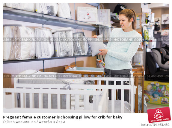 Pregnant female customer is choosing pillow for crib for baby. Стоковое фото, фотограф Яков Филимонов / Фотобанк Лори
