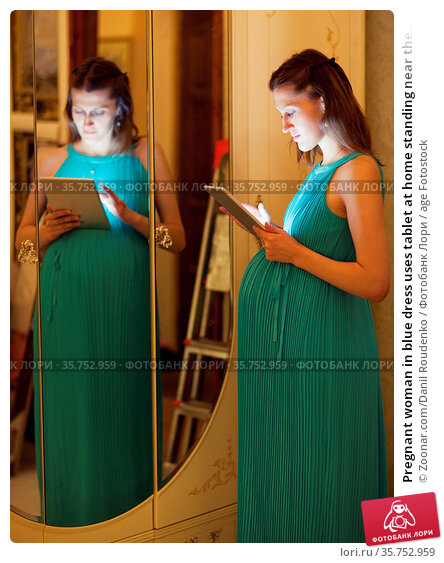 Pregnant woman in blue dress uses tablet at home standing near the... Стоковое фото, фотограф Zoonar.com/Danil Roudenko / age Fotostock / Фотобанк Лори