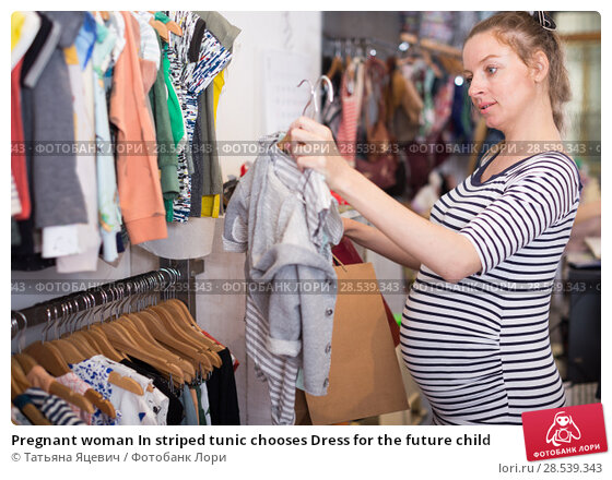 Купить «Pregnant woman In striped tunic chooses Dress for the future child», фото № 28539343, снято 6 апреля 2017 г. (c) Татьяна Яцевич / Фотобанк Лори