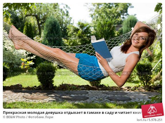 Купить «Прекрасная молодая девушка отдыхает в гамаке в саду и читает книгу», фото № 5978251, снято 19 октября 2018 г. (c) BE&W Photo / Фотобанк Лори