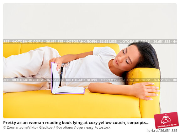 Pretty asian woman reading book lying at cozy yellow couch, concepts... Стоковое фото, фотограф Zoonar.com/Viktor Gladkov / easy Fotostock / Фотобанк Лори