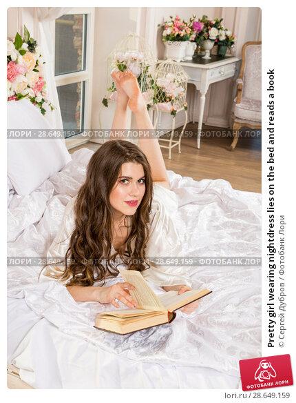 Купить «Pretty girl wearing nightdress lies on the bed and reads a book», фото № 28649159, снято 1 апреля 2018 г. (c) Сергей Дубров / Фотобанк Лори