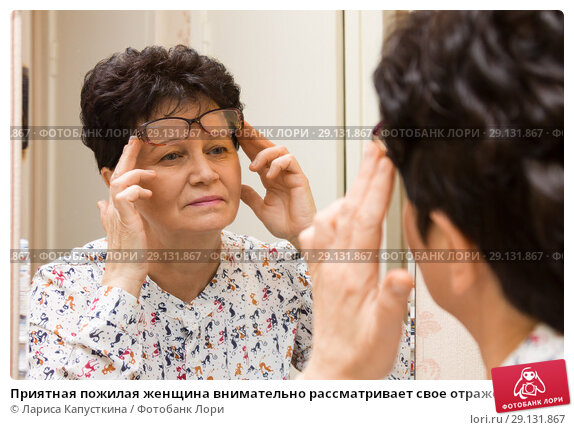 Приятная пожилая женщина внимательно рассматривает свое отражение в зеркале. Стоковое фото, фотограф Лариса Капусткина / Фотобанк Лори